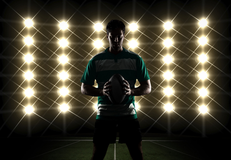 Rugby player silhouette in front of lights in a green uniform.