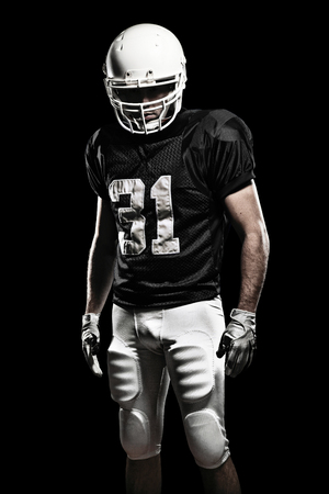 Football Player with a black uniform, on a black background. photo