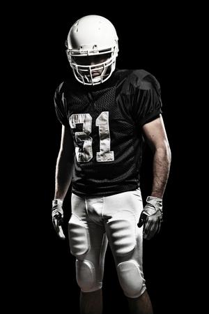 jugador de futbol: Jugador de f�tbol con un uniforme negro, sobre un fondo negro.