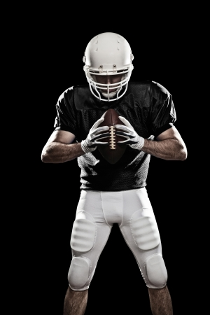 sports uniform: Football Player with a black uniform, on a black background. Stock Photo