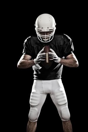 uomini di colore: Giocatore di calcio con una uniforme nera, su sfondo nero. Archivio Fotografico