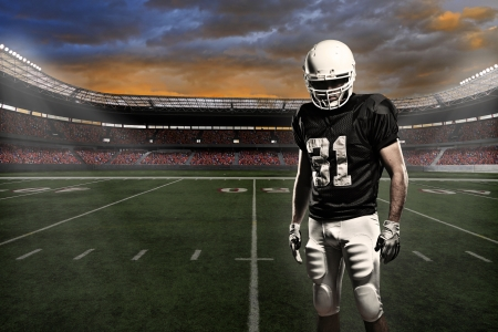 football stadium: Football player with a black uniform, in a stadium.