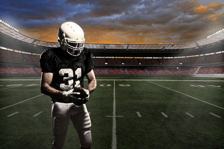 Football player with a black uniform, in a stadium.
