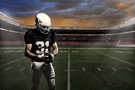 uniforme de futbol: Jugador de f�tbol con un uniforme negro, en un estadio. Foto de archivo