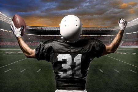 Football Player with a black uniform celebrating on a stadium. Standard-Bild