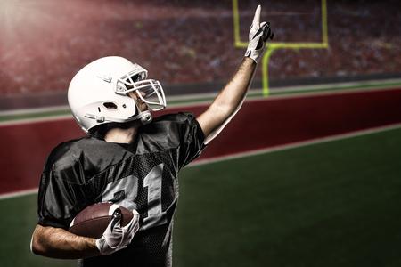 jugador de futbol: Jugador de f�tbol con un uniforme negro que celebra en un estadio. Foto de archivo