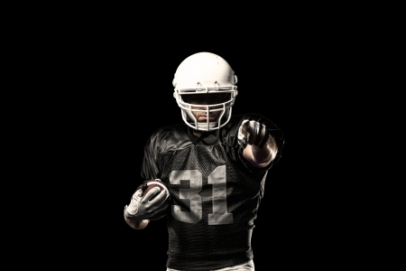 black people: Football Player with a black uniform, on a black background. Stock Photo