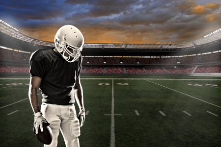 football player: Football player with a black uniform, in a stadium.