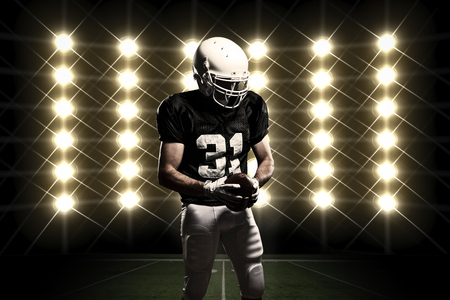 Football Player with a black uniform celebrating in front of lights. Standard-Bild