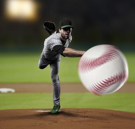 Pitcher Baseball Player on a Green Uniform on baseball Stadium.