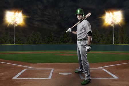 Baseball Player on a Green Uniform on baseball Stadium. Stock Photo