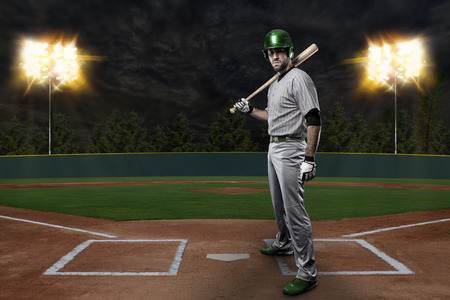 Baseball Player on a Green Uniform on baseball Stadium. photo