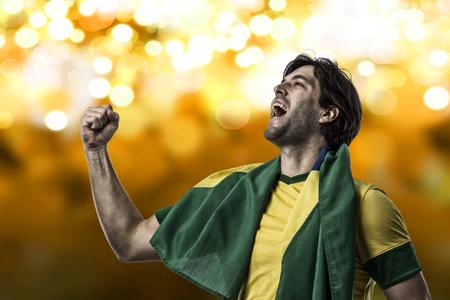 Brazilian soccer player, celebrating on a Yellow lights background.