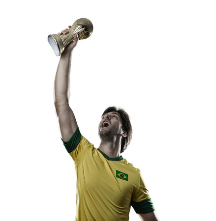 Brazilian soccer player, celebrating the championship with a trophy in his hand, on a white . Stock Photo