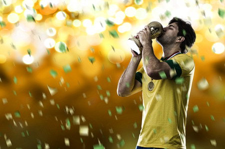 world cup: Brazilian soccer player, celebrating the championship with a trophy in his hand, on a yellow background.