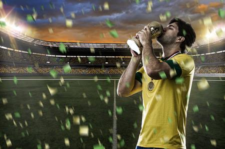 Joueur de football brésilien, célébrant le championnat avec un trophée à la main. Banque d'images