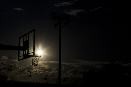 silhouette of a basketball hoop, under the sunset.