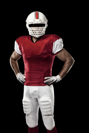football players: Jugador de f�tbol con un uniforme rojo sobre un fondo negro.