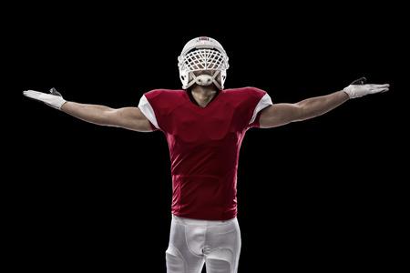 jugando futbol: Jugador de f�tbol con un uniforme rojo que celebra, sobre un fondo Negro.