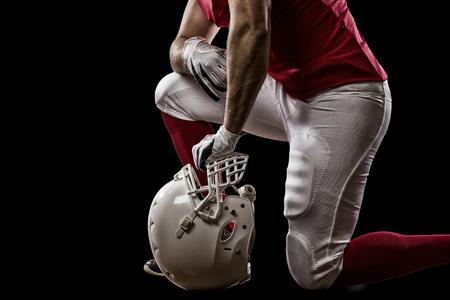jugador de futbol: Jugador de f�tbol con un uniforme rojo de rodillas, sobre un fondo Negro.