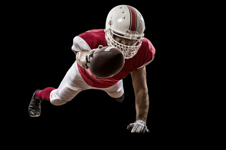 football tackle: Football Player with a red uniform scoring on a Black background. Stock Photo
