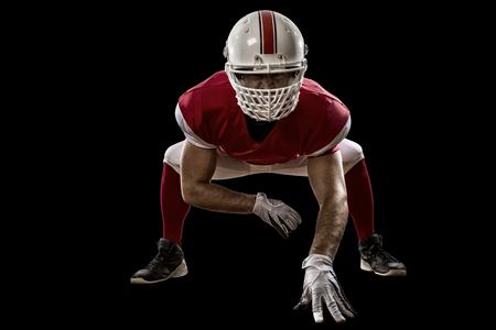 jugador de futbol: Jugador de f�tbol con un uniforme rojo en la l�nea de scrimmage, sobre un fondo Negro.