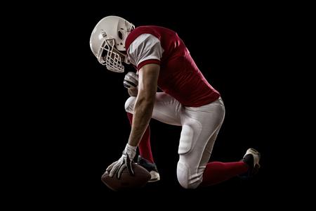 jugando futbol: Jugador de f�tbol con un uniforme rojo de rodillas, sobre un fondo Negro.