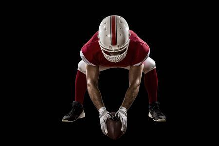 football players: Jugador de f�tbol con un uniforme rojo en la l�nea de scrimmage, sobre un fondo Negro.
