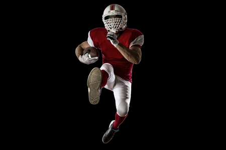 football tackle: Football Player with a red uniform Running on a Black background. Stock Photo