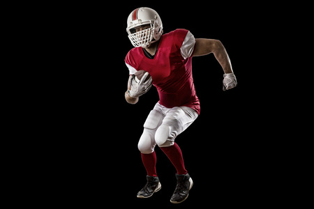 Football Player with a red uniform Running on a Black background. Stock Photo
