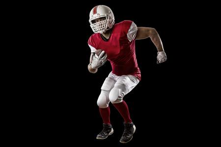 jugador de futbol: Jugador de f�tbol con un uniforme rojo que se ejecuta en un fondo Negro.