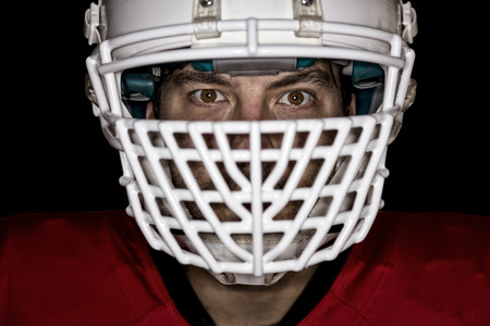 football tackle: Close up in the eyes of a Football Player with a red uniform on a Black background. Stock Photo