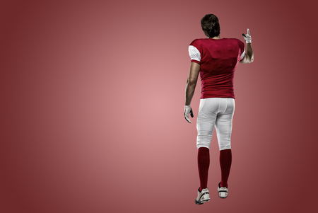 Football Player with a red uniform walking, showing his back on a red background.