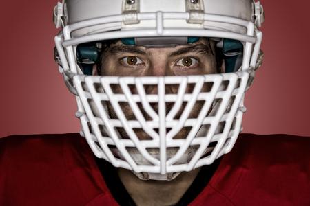 jugador de futbol: Close up en los ojos de un jugador de f�tbol con un uniforme rojo sobre un fondo rojo. Foto de archivo