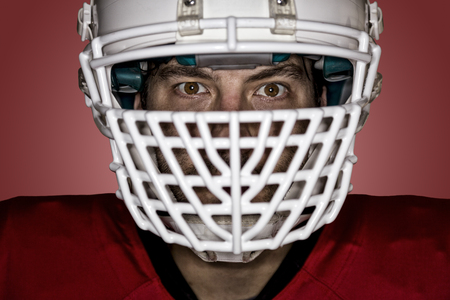 football tackle: Close up in the eyes of a Football Player with a red uniform on a red background.