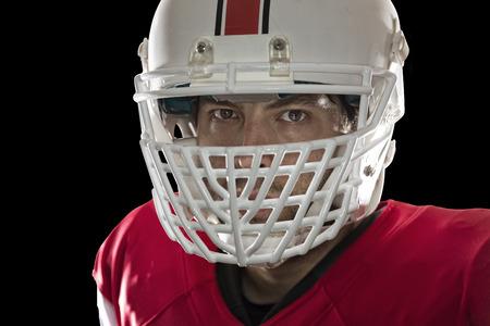 jugador de futbol: Close up en los ojos de un jugador de f�tbol con un uniforme rojo sobre un fondo Negro.