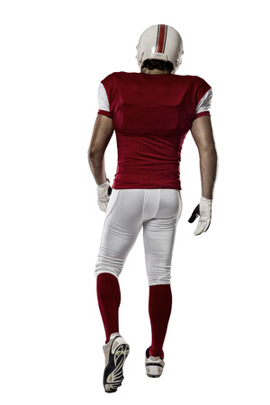 Football Player with a red uniform walking, showing his back on a white background.