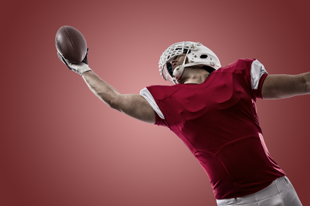 football tackle: Football Player with a red uniform making a catch on a red background.
