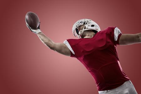 jugando futbol: Jugador de f�tbol con un uniforme rojo que hace una captura sobre un fondo rojo.