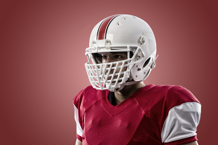 player: Close up of a Football Player with a red uniform on a red background. Stock Photo