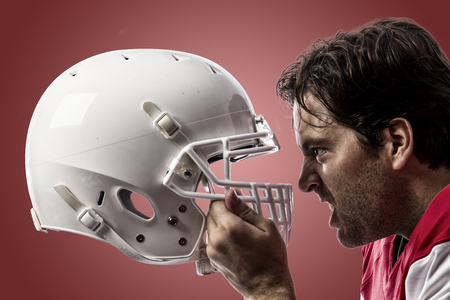 football tackle: Close up of a Football Player with a red uniform on a red background. Stock Photo