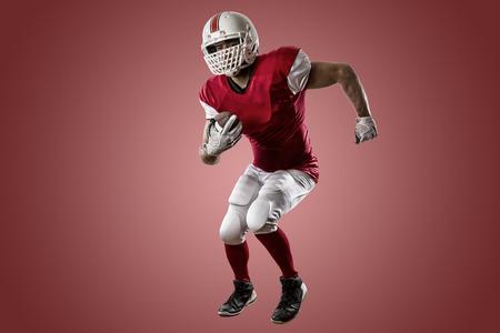 football players: Jugador de f�tbol con un uniforme rojo que se ejecuta en un fondo rojo.
