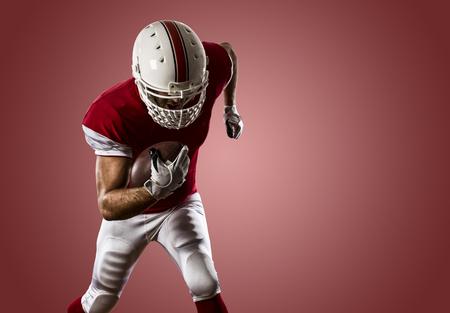 jugador de futbol: Jugador de f�tbol con un uniforme rojo que se ejecuta en un fondo rojo.