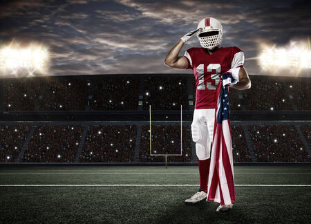 player: Football Player with a red uniform saluting with a american flag, on Stadium. Stock Photo