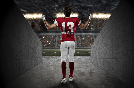 football tackle: Football Player with a red uniform walking out of a Stadium tunnel.