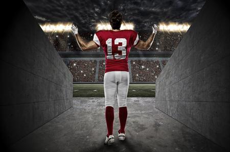 jugando futbol: Jugador de f�tbol con un uniforme rojo que sale de un t�nel Stadium.