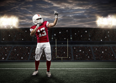 football tackle: Football Player with a red uniform making a selfie on a stadium.