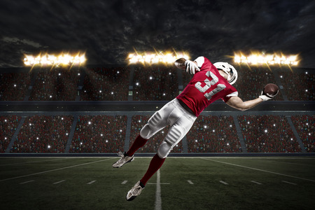 football tackle: Football Player with a red uniform catching a ball on a stadium.