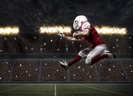 black white red: Football Player with a red uniform Running on a stadium. Stock Photo