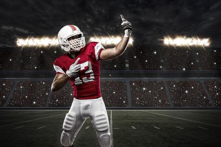 jugador de futbol: Jugador de f�tbol con un uniforme rojo haciendo una Autofoto en un estadio.